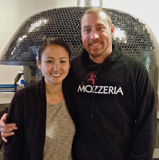 Melody (left) and Russell (right) standing and smiling. Russell is wearing a sweatshirt with the Mozzeria logo.